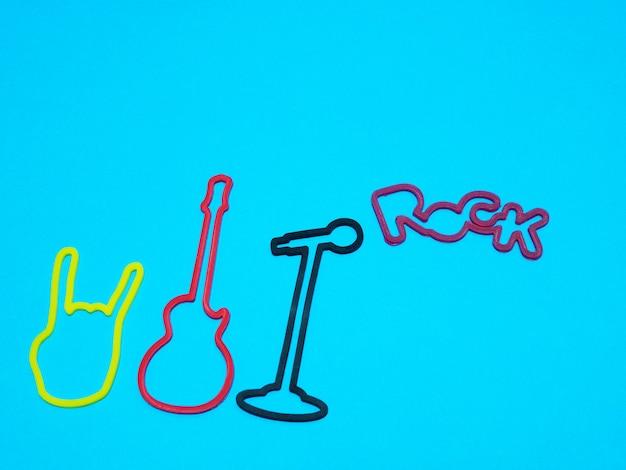 Rockmusikkonzept - gitarre, mikrofon, rockwort und teufelshorn