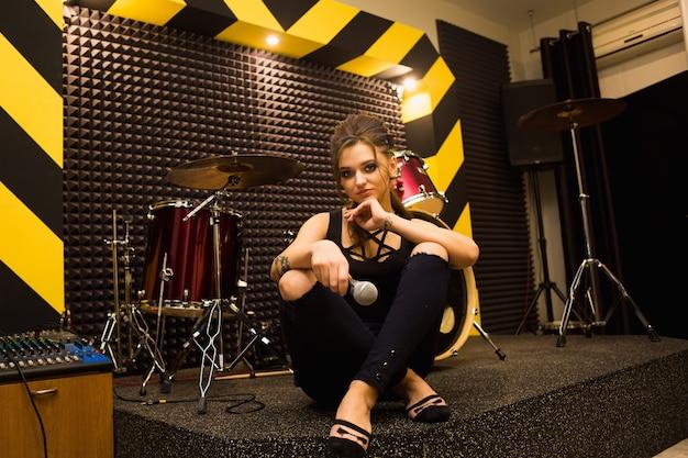 Rocksänger, der den sound im professionellen studio mit mikrofon an der gestreiften wand aufnimmt