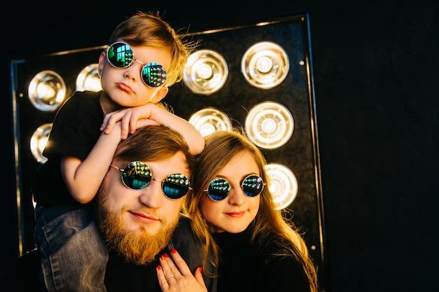 Rockstar-familie in schwarzer kleidung und brille im licht der strahlen. rock-n-roll-familiengeschichte