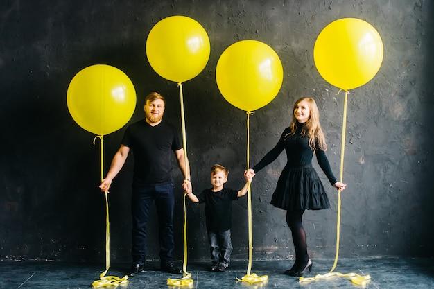 Rockstar-familie mit großen gelben luftballons. stilvolle familie in den schwarzen kleidern auf einem schwarzen hintergrund.