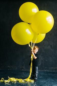 Rockstar-junge mit großen gelben luftballons. stilvolles baby in den schwarzen kleidern auf einem schwarzen hintergrund