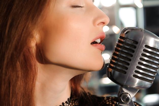 Rockstar. sexy mädchen, das im retro- mikrofon singt.