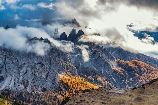 Rocky mountains bedeckt mit wolken und bunten bäumen in der herbstsaison, dolomitenalpen, italien