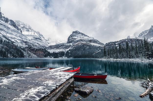 Rocky mountains mit rotem kanu am hölzernen pier