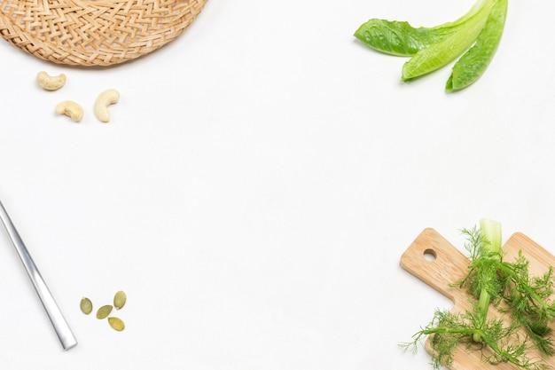 Römersalat hinterlässt einen fenchelzweig und eine weidenplatte in den ecken des rahmens