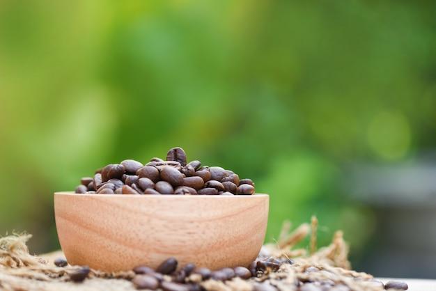 Röstkaffeebohnen auf hölzerner schüssel und kaffeebohnen des sacks / der nahaufnahme auf naturgrün