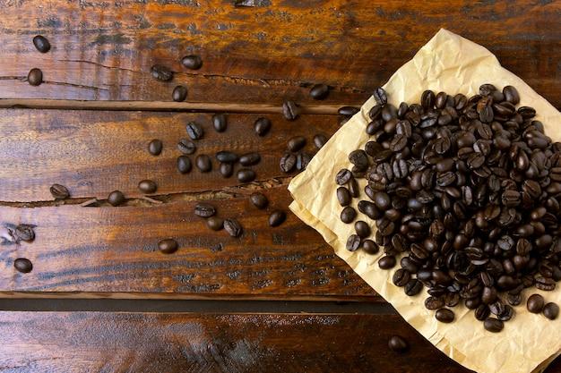 Röstkaffeebohnen auf papier auf rustikalem holztisch