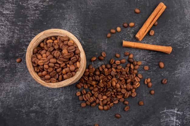 Röstkaffeebohnen in der kleinen hölzernen schüssel und im zimt auf schwarzer oberfläche