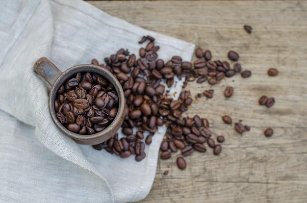 Röstkaffeebohnen in einem einfachen keramischen becher auf einer hölzernen, draufsicht