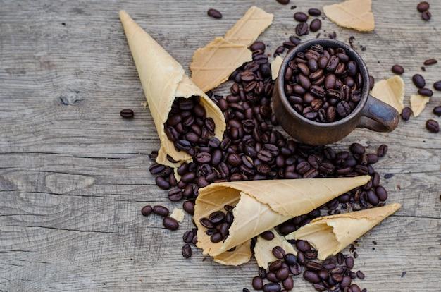 Röstkaffeebohnen in einem keramischen becher und in zuckerwaffelkegeln auf einem holz