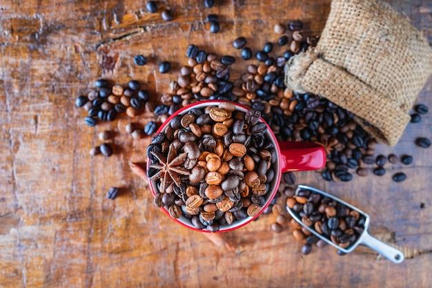 Röstkaffeebohnen in einer roten kaffeetasse auf einem holztisch