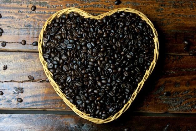 Röstkaffeebohnen innerhalb des korbes mit herzform auf rustikalem holztisch