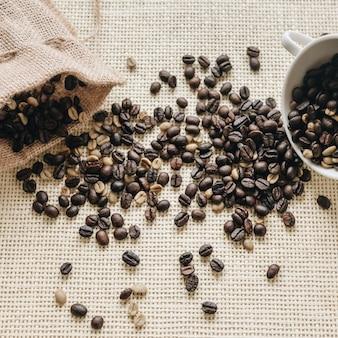 Röstkaffeebohnen mit sack und keramikschale
