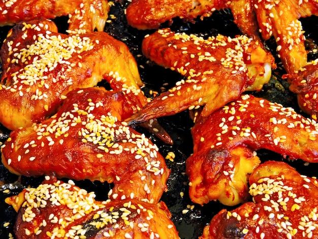 Rötliche gebackene flügel mit samen des indischen sesams. gebackene hühnerflügel auf einem backblech. barbecue chicken wings.