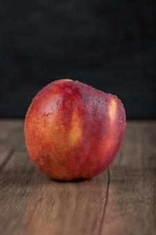 Rötliche pfirsiche auf holztisch isoliert.