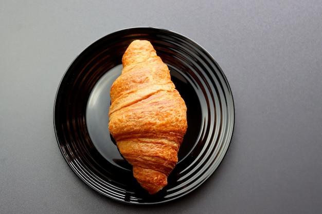 Rötliches croissant auf einem schwarzen teller auf einem grauen. Premium Fotos