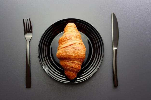 Rötliches croissant auf einem schwarzen teller mit einer gabel und einem messer auf einem grauen hintergrund Premium Fotos