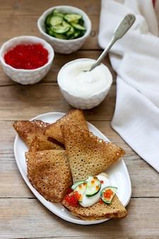 Roggen- und vollkornpfannkuchen, serviert mit sauerrahm, kaviar und gurken. rustikaler stil.