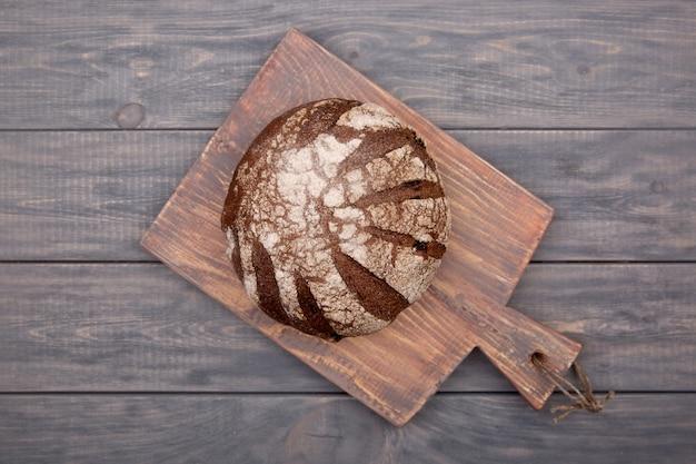 Roggenbrot rundes brot auf einem holzbrett mit einem messer aus rustikalem holz. draufsicht.