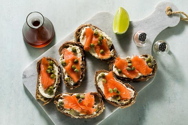 Roggenbrot-sandwiches mit geräucherten salmonnd-kapern auf marmorbrett und sesamöl mit limettenscheiben