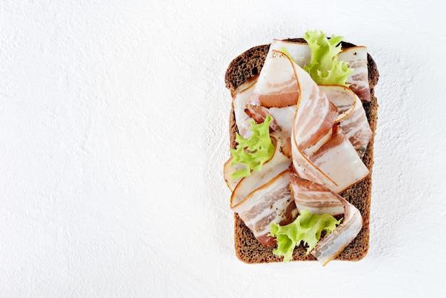 Roggenbrot-toast mit speckscheiben (pancetta, schmalz), knoblauch und italienischen kräutern, antipasti, italienischer bruschetta (crostini)