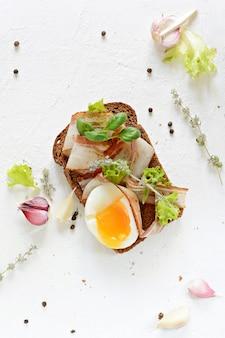 Roggenbrot-toast mit speckscheiben (pancetta, schmalz), weichgekochtem ei, knoblauch und italienischen kräutern, antipasti, italienischer bruschetta (crostini)