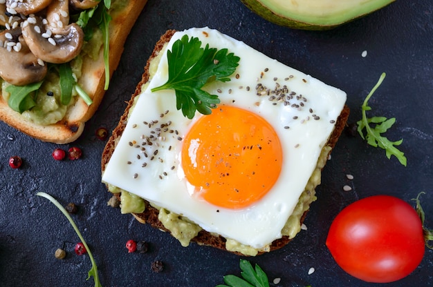 Roggentoast mit zerdrückter avocado, spiegelei, frischer tomate, kräutern. leckeres frühstück. richtige ernährung. sandwich mit ei. die draufsicht