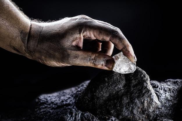 Rohdiamant, der von der hand des bergmanns entfernt wird, bergbaukonzept