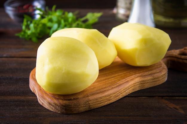Rohe abgezogene und geschnittene kartoffeln auf einem alten verwitterten holztisch.