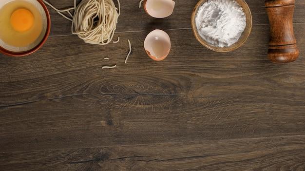 Rohe asiatische hausgemachte nudel mit eiern, salz, eierschale und mehl, kopienraum für tapeten oder hintergründe