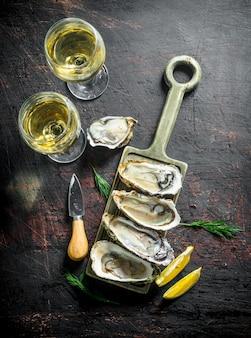 Rohe austern auf einem schneidebrett mit zwei gläsern weißwein auf rustikalem tisch