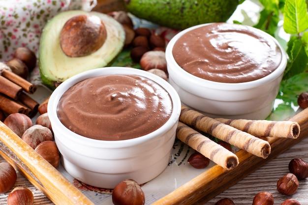 Rohe avocado-schokoladenmousse mit schokolade und minze, selektiver fokus. gesundes veganes schokoladendessert.