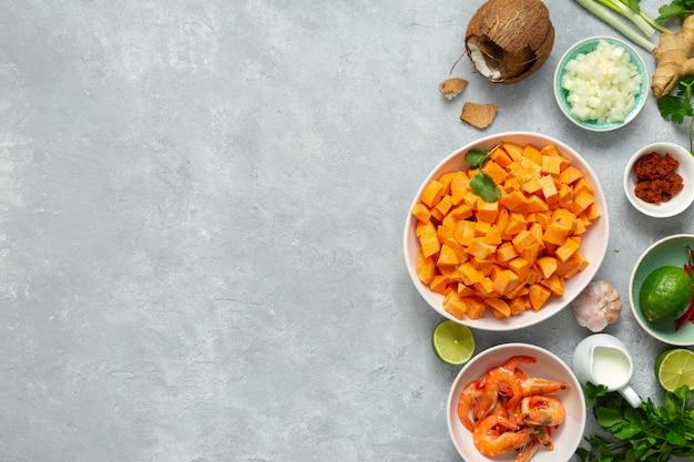 Rohe bestandteile, die draufsichthintergrund der süßkartoffelsuppengarnelen kochen