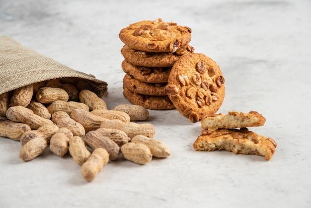 Rohe bio-erdnüsse und leckere kekse auf marmortisch.