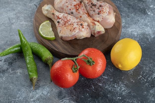 Rohe bio-hähnchenschenkel mit zutaten zum kochen auf einem hölzernen schneidebrett.
