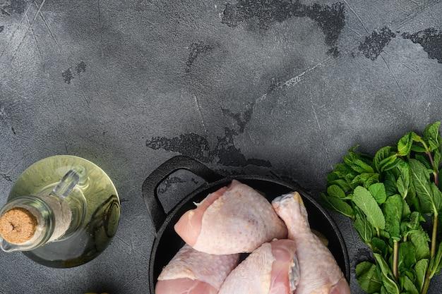 Rohe bio-hähnchenschenkel mit zutaten zum kochen, marinieren, auf bratpfanne aus gusseisen, auf grauem tisch, draufsicht flach legen