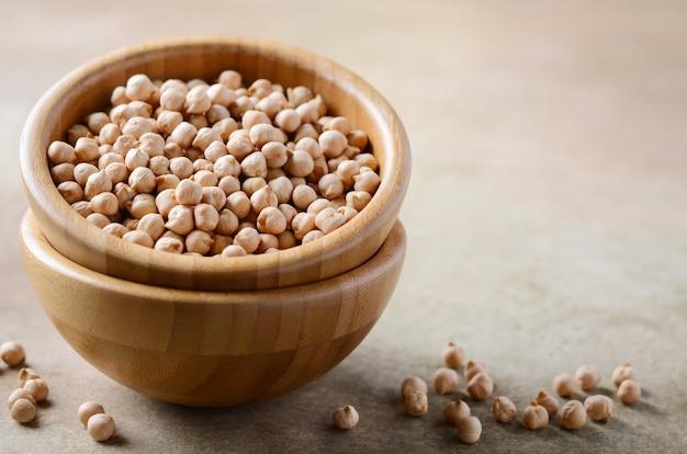 Rohe bio-kichererbsen in einer holzschale, gesunde vegane vegetarische lebensmittelzutat.