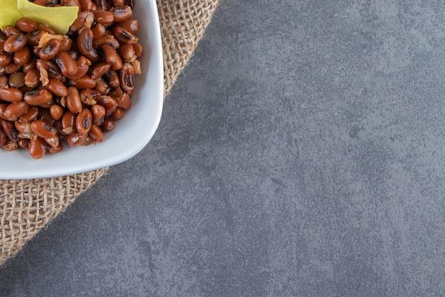 Rohe bohnen und lasagneblätter in einer schüssel auf der leinenserviette, auf dem blauen hintergrund.