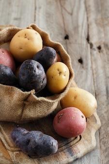 Rohe bunte kartoffeln auf einem holztisch hautnah