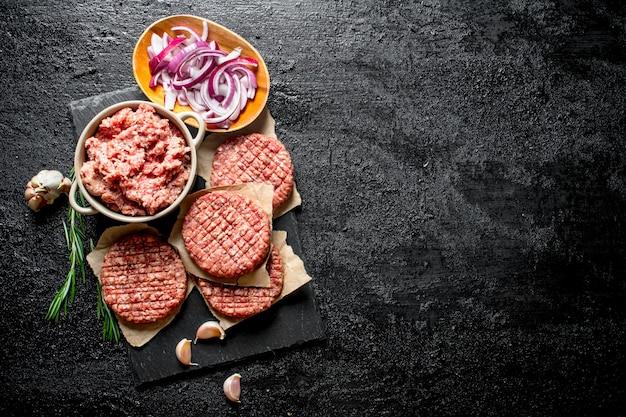 Rohe burger mit rinderhackfleisch und geschnittenen zwiebeln in schalen. auf schwarzem rustikalem hintergrund