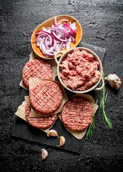Rohe burger mit rinderhackfleisch und geschnittenen zwiebeln in schalen. auf schwarzem rustikalem tisch