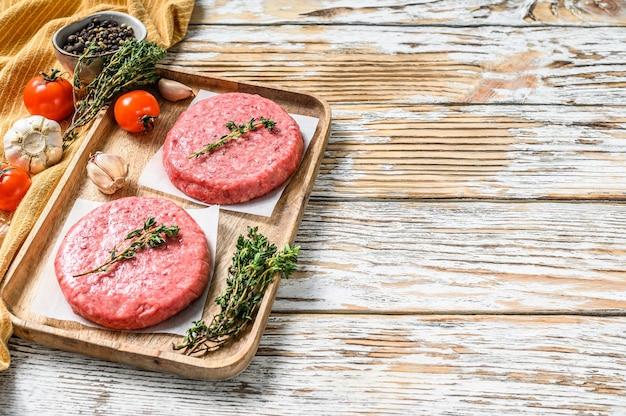 Rohe burger pastetchen. hackfleischschnitzel, rinderhackfleisch und schweinefleisch. weißer hintergrund. draufsicht. speicherplatz kopieren.