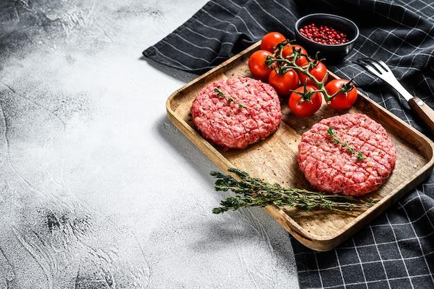 Rohe burger schnitzel, bio rinderhackfleisch. grauer hintergrund
