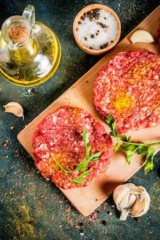 Rohe burgerkoteletts mit salz, pfeffer, öl, kräutern und gewürzen, auf dunkler tabelle, draufsicht copyspace
