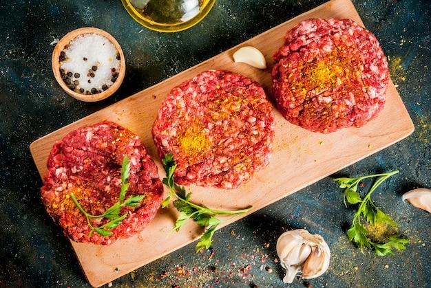 Rohe burgerkoteletts mit salz, pfeffer, öl, kräutern und gewürzen, auf dunkler tabelle, kopienraum