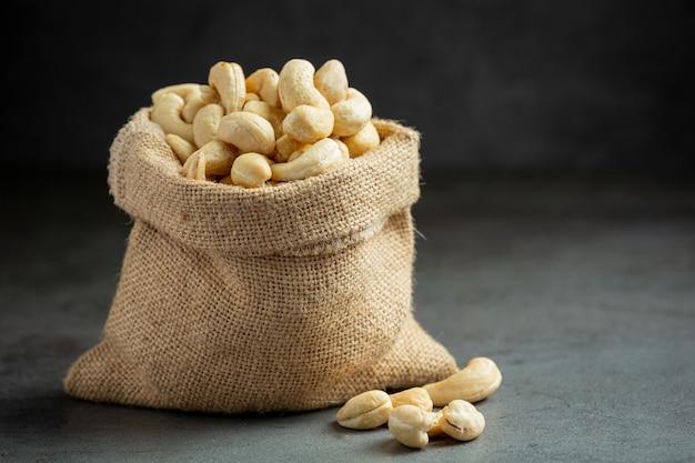 Rohe cashewnüsse im beutel auf dunklem hintergrund