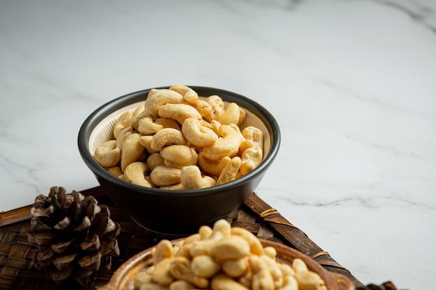 Rohe cashewnüsse in schüssel auf marmorhintergrund