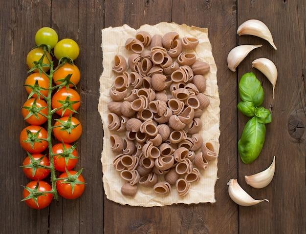 Rohe conchiglie-nudeln, basilikum und gemüse auf holztischoberansicht