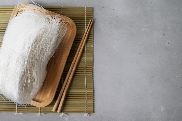 Rohe dünne reisnudeln auf bambusteller auf steinoberfläche mit stöcken