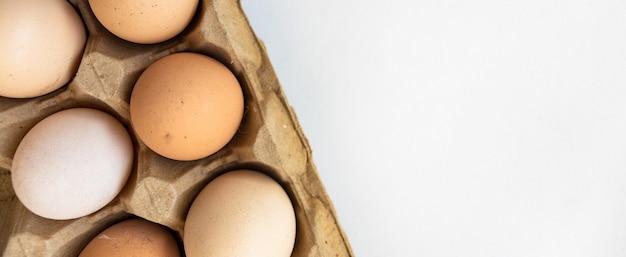 Rohe eier auf einer holzschale, auf weißem hintergrund. vertikale draufsicht von oben. isoliert